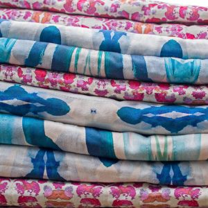 A stack of organic cotton sateen fabric by Linda Cabot Design