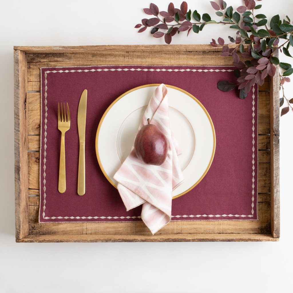 Pink and white patterned organic cotton napkin on solid merlot placemat