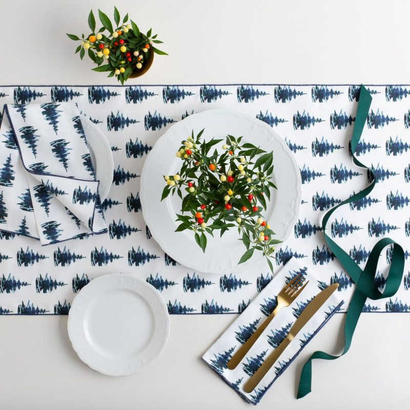 Pine tree patterned table runner with holiday decor