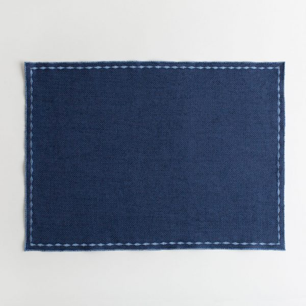 Blue placemat with white decorative stitching