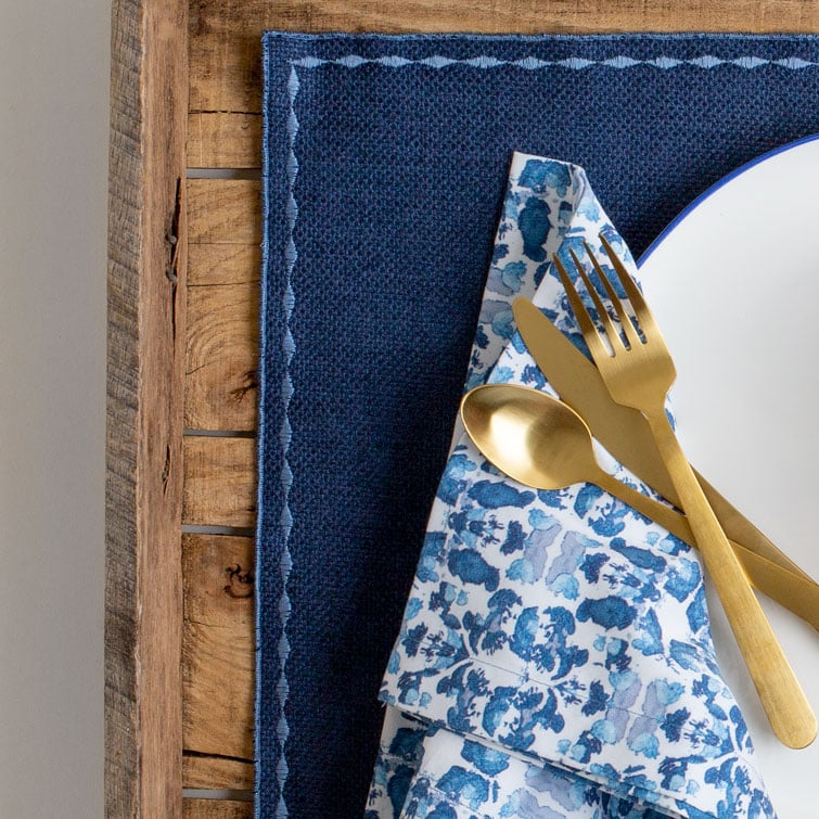 Blue place mat with organic cotton blue and white napkin and brass cutlery