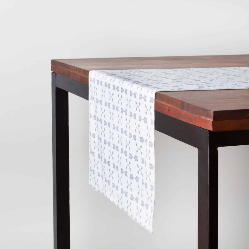 Gray and white patterned organic cotton table runner on a dark table