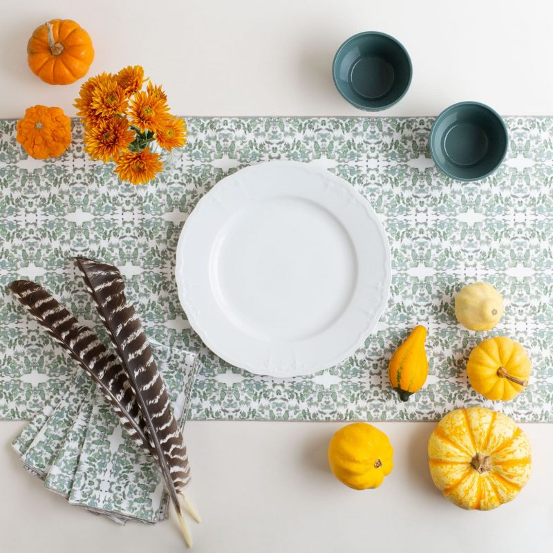 Sage and white lace patterned table runner with an autumnal table setting