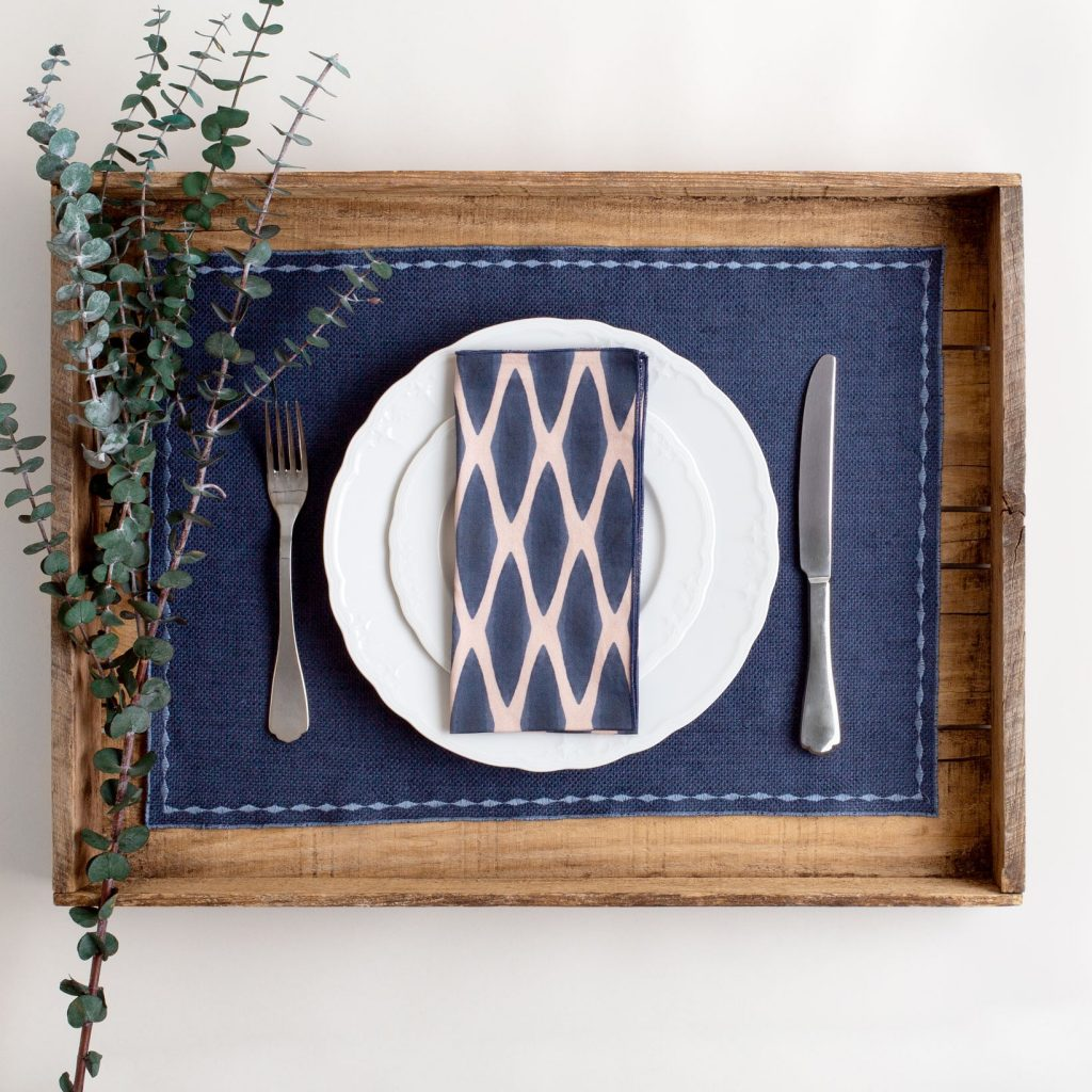 Navy and blush organic cotton napkin on solid blue placemat