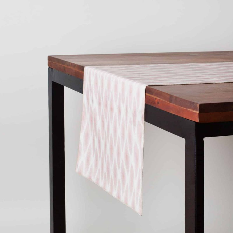 Pink and white patterned organic cotton table runner on a dark wood table